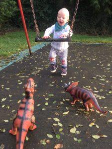 toddler playing with dinosaur